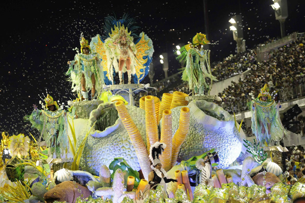 Revellers from Imperio Serrano samba school dance atop a float during the first night of the Carnival parade in Rio de Janeiro's Sambadrome